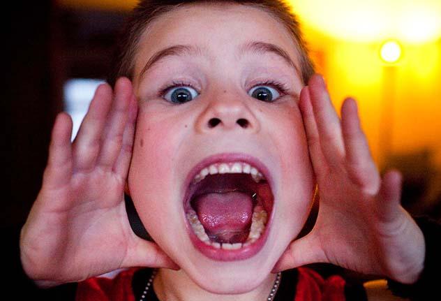 Мальчик открыл широко рот и показывает свое горло