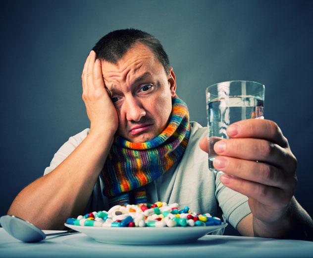 Мужчина болеет и собирается выпить кучу лекарств