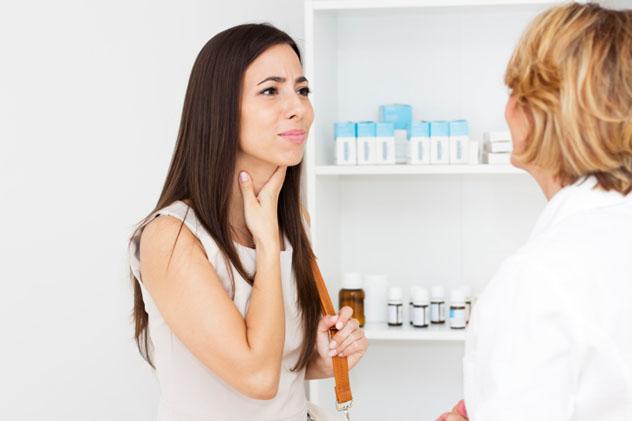 Девушка в кабинете врача жалуется на боль в горле