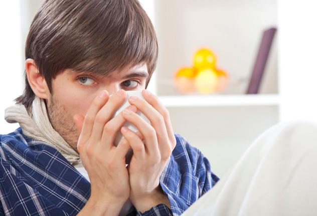 Мужчина пьет лекарство от горла