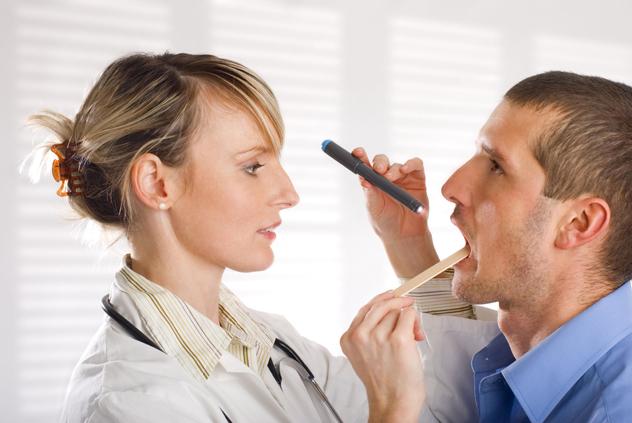 ЛОР врач осматривает горло пациенту