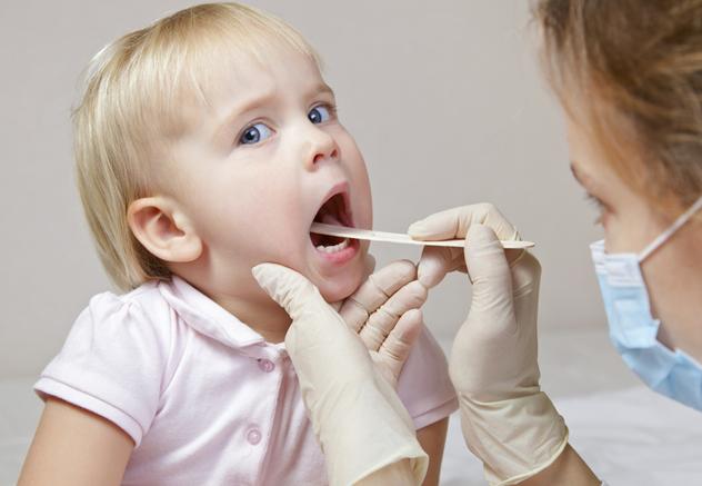 Врач осматривает горло ребенку