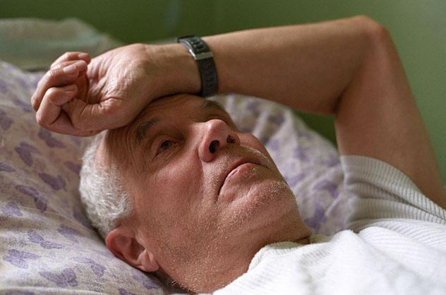 Больной мужчина лежит на кровати