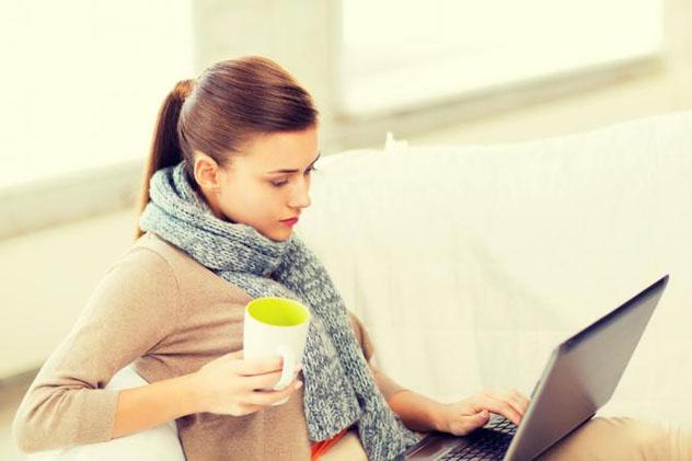 Девушка в шарфе смотрит в ноутбук