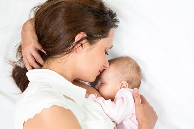 Мама кормит грудью новорожденного ребенка
