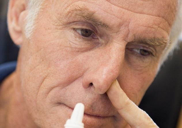 Мужчина капает капли в нос