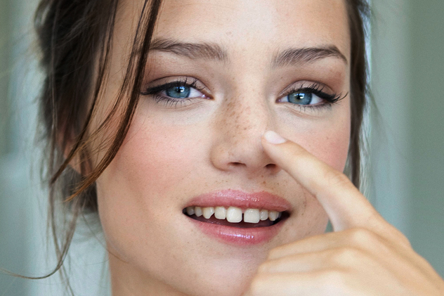 Девушка улыбается и показывает на свой нос