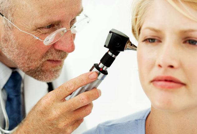 Врач осматривает ухо пациентке