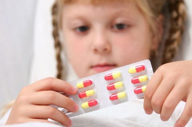 Девочка держит в руках упаковку с таблетками