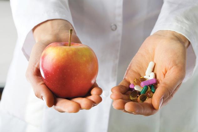 Врач дает яблоко и таблетки