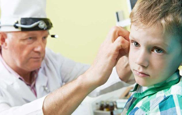 Врач обследует ухо мальчика