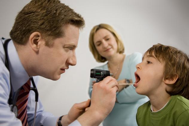 Врач осматривает горло пациенту