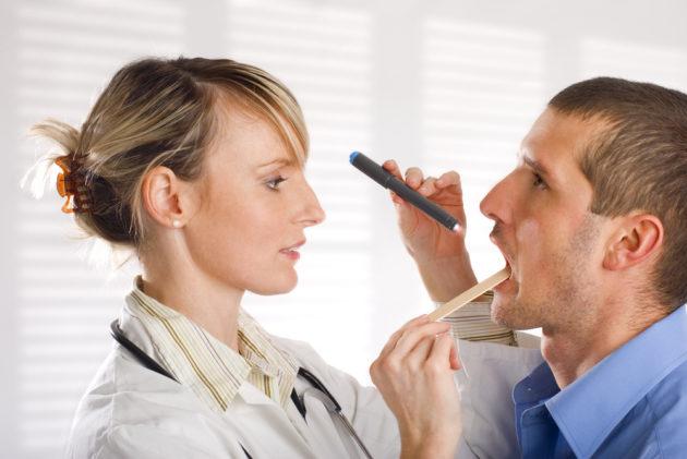 Доктор осматривает горло при лор-заболевании